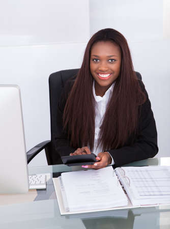 business advisor: Portrait of confident businesswoman calculating tax at desk in office Stock Photo