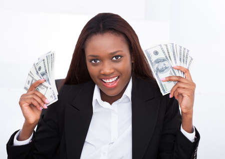 woman holding money: Portrait of surprised businesswoman holding money fan in office