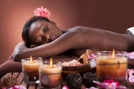 african american spa: Side view portrait of smiling young woman relaxing at beauty spa Stock Photo