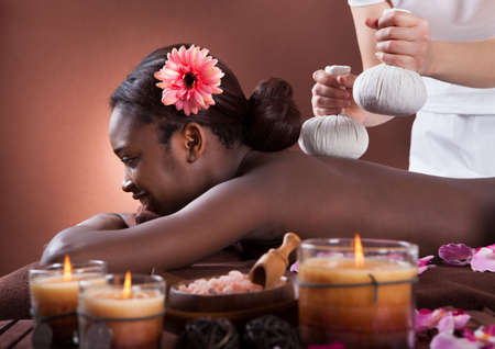 Side view of African American woman enjoying herbal massage at spa salon
