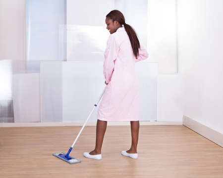 Full length of female housekeeper mopping floor in hotel photo