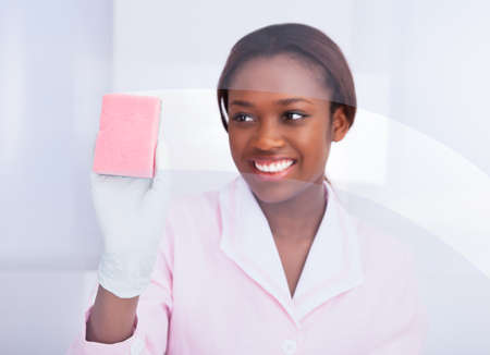 office equipment: Happy African American female housekeeper cleaning glass in hotel Stock Photo
