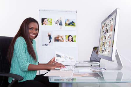 Young female editor using digital tablet at photo agency