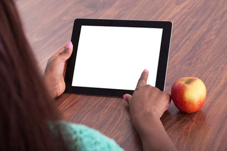 Cropped image of female teacher using digital tablet at classroom desk photo