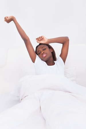 raised arms: Portrait of young African American woman stretching in bed at home
