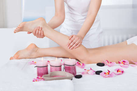 rejuvenate: Young Woman Getting Feet Massage Treatment At Spa Stock Photo