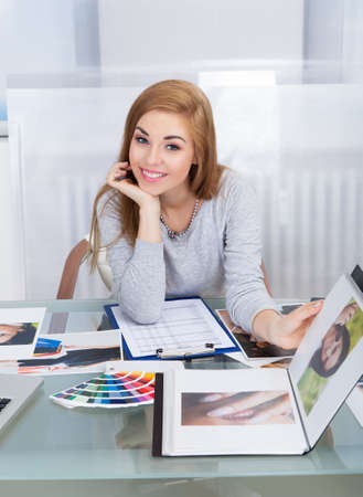 clipboards: Portrait Of A Happy Young Woman Holding Photo Album