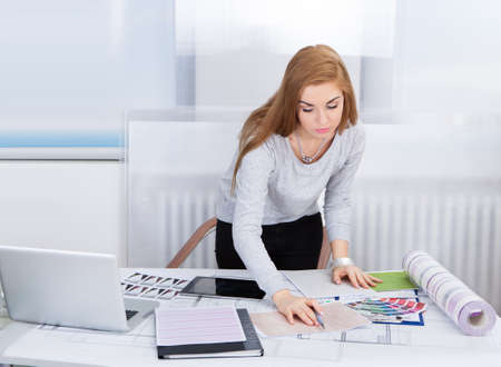 Portrait Of A Young Woman Working At Office Desk