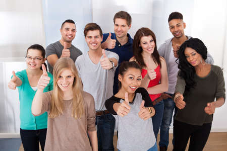 Group portrait of confident multiethnic university students gesturing thumbs up in classroom photo