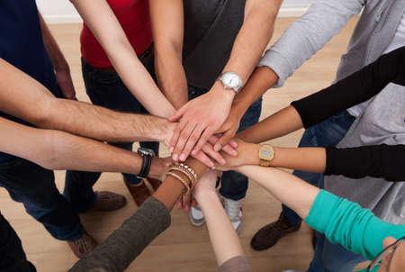 Vista de ángulo alto de los estudiantes universitarios multiétnicas apilamiento manos en el aula