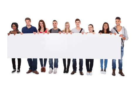 university sign: Full length portrait of confident multiethnic college students displaying blank billboard against white background