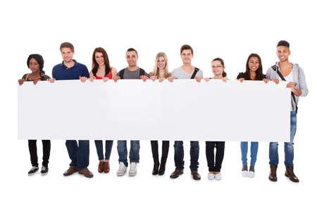 colegios: Retrato de cuerpo entero de los estudiantes universitarios multi�tnicas confianza que muestra la cartelera en blanco contra el fondo blanco