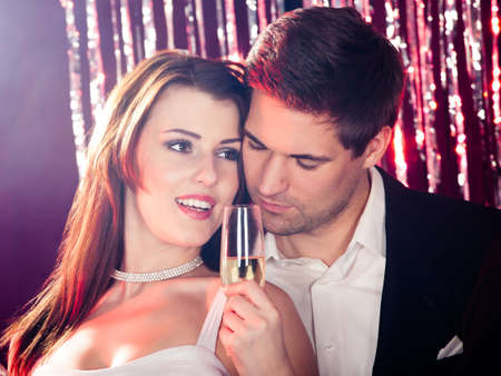 Romantic young couple enjoying champagne at nightclub photo
