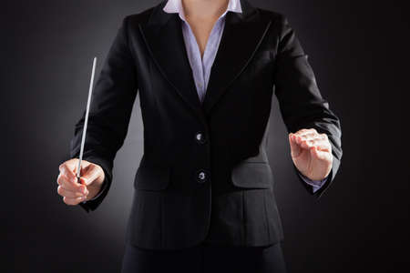 Close-up Of Female Orchestra Conductor Holding Baton Over Black Background photo