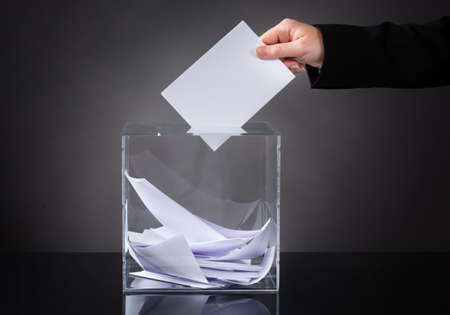 Close-up Of Hand Putting Ballot In Glass Box photo