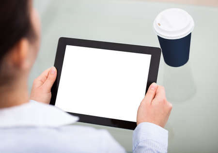 Close-up Of Businesswoman Holding Blank Screen Digital Tablet And Disposable Cup photo