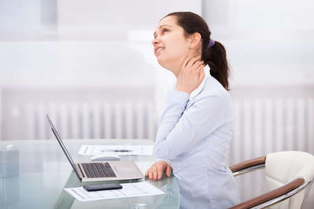 Young Businesswoman Having Pain In Neck At Workplace photo