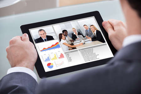 training device: Close-up Of Businessman Video Conferencing With Co-worker About Progress Chart
