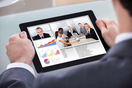 sala de reuniones: Primer plano del hombre de negocios Videoconferencia con los compañeros de trabajo sobre el progreso Gráfico