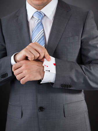Close-up Of Businessperson Hiding Poker Card In The Sleeve photo