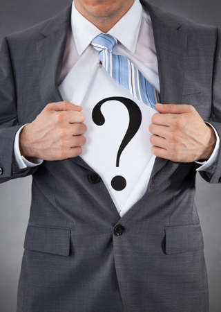 Businessman Pulling Back Shirt To Reveal Question Mark Sign photo