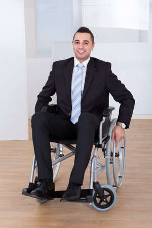 Full length portrait of happy businessman in wheelchair at office photo