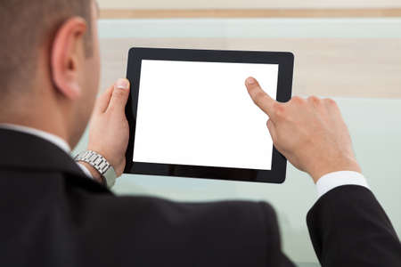 Cropped image of businessman using digital tablet in office photo