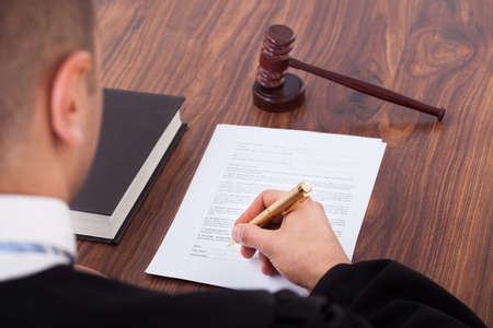 government regulations: Cropped image of judge signing document in courtroom Stock Photo