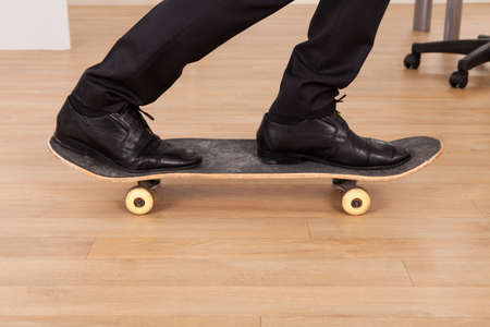 Low section of businessman on skateboard in office photo