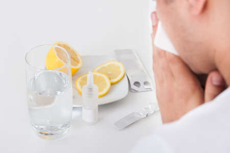 Cropped image of man suffering from cold with medicines and water glass on table photo
