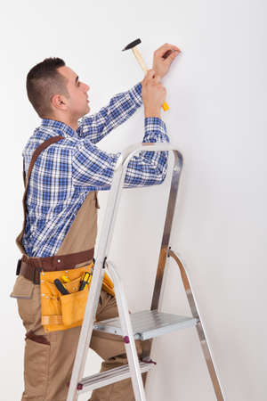 Side view of male repairman on ladder hammering wall with nail photo