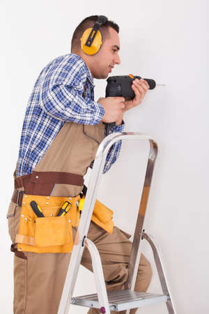 Side view of repairman on stepladder drilling hole in wall photo