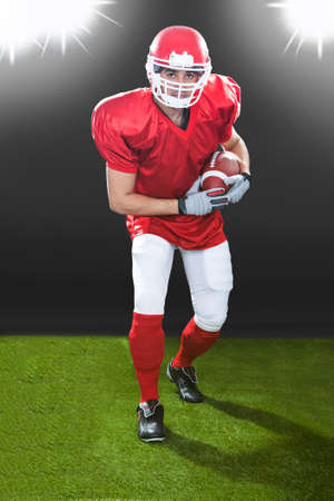 Full length portrait of confident American football player playing on field at night photo