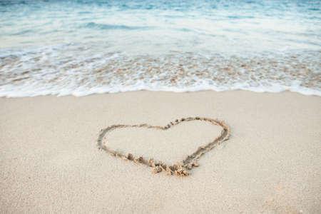 heart in sand: Heart shape drawn in sand on beach Stock Photo