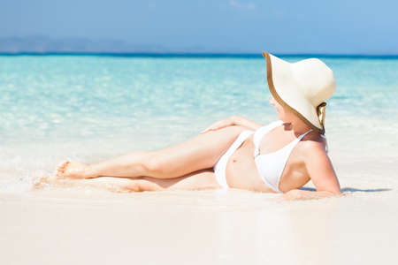 Portrait of sexy young woman wearing sunhat lying on sunny beach photo