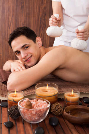 Portrait of young man receiving massage with stamps in spa photo