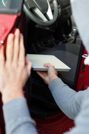robo de autos: Imagen recortada de ladrón robando portátil de coche Foto de archivo