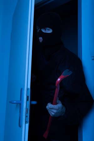 noiseless: Thief holding crowbar while secretly entering into house Stock Photo