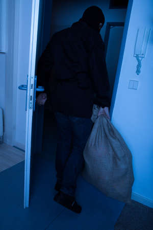exiting: Full length of thief carrying sack while exiting house