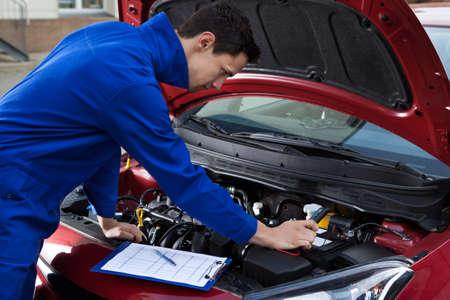 mantenimiento: Vista lateral de la joven mec�nico en el coche de la reparaci�n de uniforme Foto de archivo
