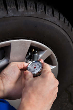 Cropped image of mechanic checking tire pressure using gauge photo