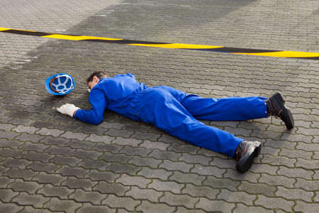 Full length of young unconscious technician lying on street photo