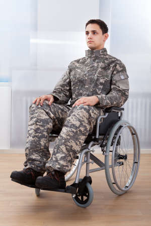 wheelchair access: Full length of patriotic soldier sitting on wheel chair at home