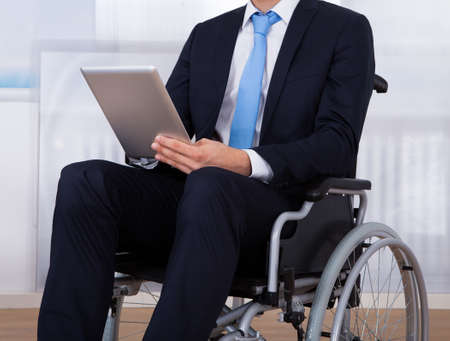 wheelchair access: Close-up image of disabled businessman using digital tablet on wheelchair in office