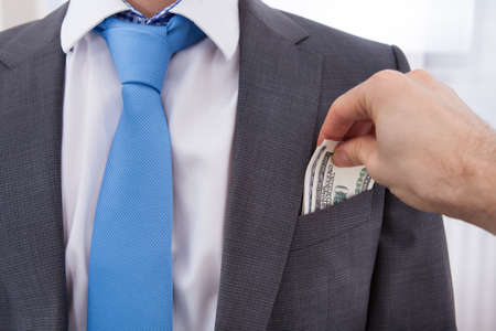putting money in pocket: Hand bribing businessman by putting money in his pocket