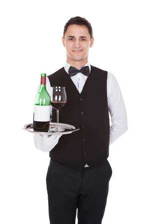 Portrait of confident young waiter holding tray with glass of red wine and bottle against white background photo