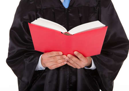 Midsection of judge holding statute book against white background photo