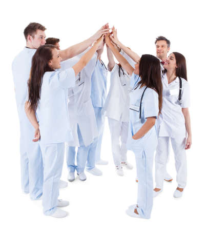 doc: Large group of motivated doctors and nurses standing in a circle giving a high fives gesture with their hands meeting in the centre  conceptual of teamwork isolated on white Stock Photo