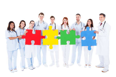 doc: Medical team of a large group of diverse doctors  physicians and nurses in white uniforms standing in a row holding colorful puzzle pieces conceptual of teamwork  challenge and problem solving