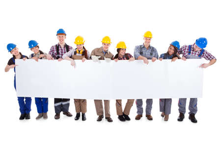 Large diverse multiethnic group of workmen and women standing in a line holding a long blank white banner with copyspace for your text isolated on white